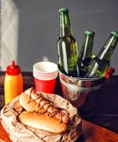 Classic American hot dogs with mustard. next to fried bacon and a bottle of beer.  stock photos