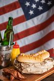 Classic American hot dogs with mustard. next to fried bacon and a bottle of beer. The whole composition against the background of the American flag stock photography