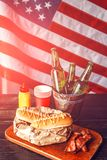 Classic American hot dogs with mustard. next to fried bacon and a bottle of beer. The whole composition against the background of the American flag royalty free stock photo