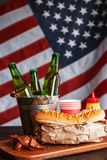 Classic American hot dogs with mustard. next to fried bacon and a bottle of beer. The whole composition against the background of the American flag royalty free stock photos