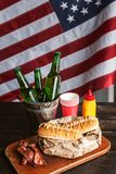 Classic American hot dogs with mustard. next to fried bacon and a bottle of beer. The whole composition against the background of the American flag royalty free stock photography