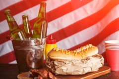Classic American hot dogs with mustard. next to fried bacon and a bottle of beer. The whole composition against the background of the American flag stock photo