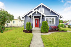 Classic American house with siding trim and red entry door. Classic American house exterior with siding trim, red entry door and concrete floor porch. Northwest stock image