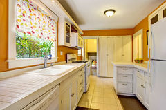 Classic American kitchen room interior with white cabinets, tile floor. Stock Images