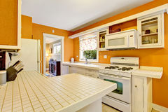 Classic American kitchen room interior with white cabinets, tile floor. Stock Image