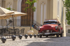 Classic american red car in Havana, Cuba. An old american car parked in front of a church in Old havana, Cuba Royalty Free Stock Photography