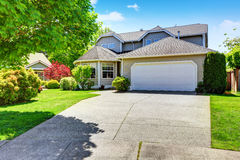 Classic American two story house exterior with garage, driveway and well kept garden Royalty Free Stock Photos