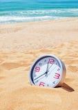 Classic analog clocks on the beach near the sea. Stock Photos