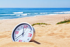 Classic analog clocks in the sand on the beach near the sea. Stock Photo