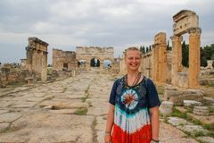 A classic antique Greek theater in Pamukkale, Denizli, Turkey and a white young woman in a hippie dress stock image