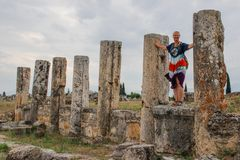 A classic antique Greek theater in Pamukkale, Denizli, Turkey and a white young woman in a hippie dress royalty free stock image