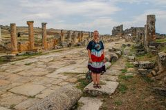 A classic antique Greek theater in Pamukkale, Denizli, Turkey and a white young woman in a hippie dress stock photo