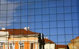 Classic architecture building reflected distorted in a modern building glass wall. stock photos