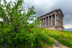 Classic architecture, Pagan Temple Of Garni (Armenia). Hellenistic architecture, the Pagan Temple of Garni (Armenia) in the green foliage of the tree Stock Images