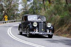 Classic Austin Sedan car. Classic black Austin Sedan car driving on road Stock Images