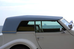 Classic automobile by the sea. Side view of classic Excalibur automobile compartment through the windows  is seen floating  ship in the sea Stock Image