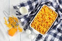 Classic Baked Homemade Macaroni and Cheese. In baking dish  with kitchen towel and grated cheddar cheese on paper on wooden table, view from above Stock Photography
