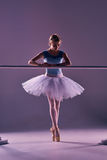 Classic ballerina posing at ballet barre Royalty Free Stock Photos
