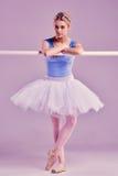 Classic ballerina posing at ballet barre Royalty Free Stock Photo