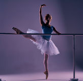 Classic ballerina posing at ballet barre Royalty Free Stock Image