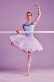 Classic ballerina posing at ballet barre. Classic ballet dancer in white tutu posing on one leg at ballet barre on a lilac background Royalty Free Stock Images