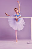 Classic ballerina posing at ballet barre. Classic ballet dancer in white tutu posing on one leg at ballet barre on a lilac background Royalty Free Stock Photo