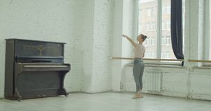 Classic ballet dancer exercising demi plie at barre. Graceful classic ballet dancer performing demi plie exersice at barre during rehearsal while training stock video