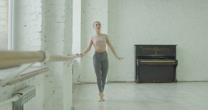 Classic ballet dancer exercising temps leve at barre. Graceful classic ballet dancer performing temps leve exersice at barre during rehearsal while training stock video footage