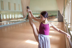 Classic ballet dancer posing at barre on rehearsal Stock Image
