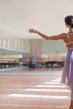 Classic ballet dancer posing at barre on rehearsal. The classic ballet dancer posing at ballet barre on a  rehearsal room background. back view Royalty Free Stock Images