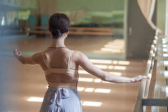 Classic ballet dancer posing at barre on rehearsal Stock Photography