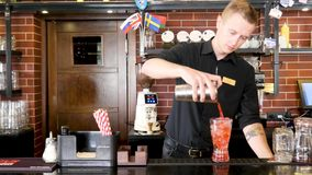 Classic bartender in black uniform pouring colorful liquid from shaker to a cocktail glass in interior classy bar