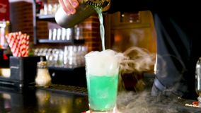 Classic bartender pouring colorful liquid from shaker to a cocktail glass with white cold smoke in interior classy bar. Classic bartender pouring colorful liquid stock footage