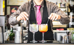 Classic bartender serving gin tonic and tequila sunrise cocktails at bar. Classic bartender serving gin tonic and tequila sunrise with straw on drink glasses Royalty Free Stock Images