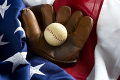 Classic Baseball Items. A grouping of classic baseball items including an anitque glove or mitt and an antique baseball on top of an American Flag royalty free stock photo