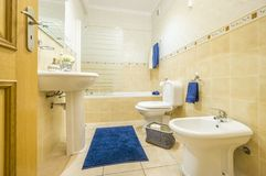 Classic bathroom with blue towels and rug. Classic bathroom in warm colors with blue towels and rug Royalty Free Stock Images