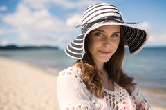 Classic beautiful woman in hat standing on beach smirking stock photos