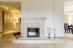 Classic beauty of a marble moulded mantel. Beautifully moulded fireplace surrounds in classic style, in a very spacious room bordering a vast anteroom Stock Image
