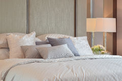 Classic bedroom interior with pillows and reading lamp on bedside table Stock Image
