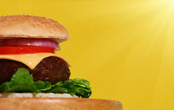 Classic beef burger on sunny yellow background Royalty Free Stock Photos