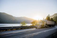 Classic big rig semi truck with bulk semi trailer driving on the. Big rig American white long haul powerful semi truck transporting commercial cargo in bulk semi royalty free stock photo