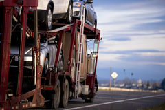 Classic big rig semi-truck car hauler with cars on road. Big truck with dark red trailer for transportation vehicles with cars in tiers on the road against the Stock Image