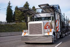 Classic big rig semi truck with car hauler semi trailer running. Classic big rig semi truck with square grille and two story compact car hauler semi trailer Stock Photography