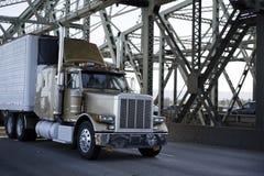 Classic big rig semi truck with refrigeration unit on reefer semi trailer running on the Interstate bridge. Big rig long haul semi trucks with refrigerator semi stock images