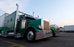 Classic big rig semi trucks in line on truck stop Royalty Free Stock Photography