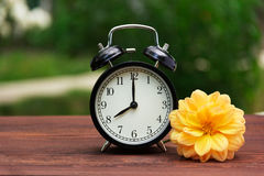 A classic black alarm clock in the garden on the table. A clock on a green natural background. Copy space. A classic black alarm clock in the garden on the table Stock Photography