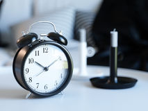 Classic black clock on a white table Royalty Free Stock Image