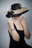 Classic black hat. A woman holding the brim of a classic black hat worn with pearls and a black dress stock photo