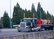 Classic black semi truck big rig flat bed commercial load Stock Image