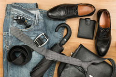 Classic black shoes and men's clothes and accessories lie on the wooden floor Stock Images